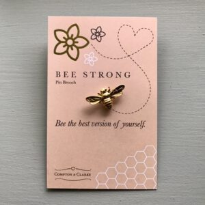 Bee Strong Pin Brooch is a gold bee on a pink card with the words bee strong