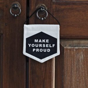 Darwin & Gray Make Yourself Proud small cream banner with the words make yourself proud on a black background